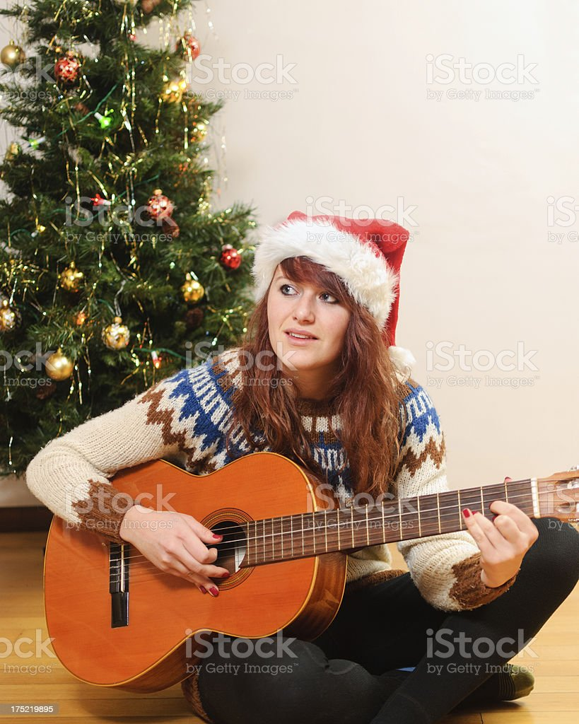 Young Woman Playing Guitar in front of Christmas Tree stock photo