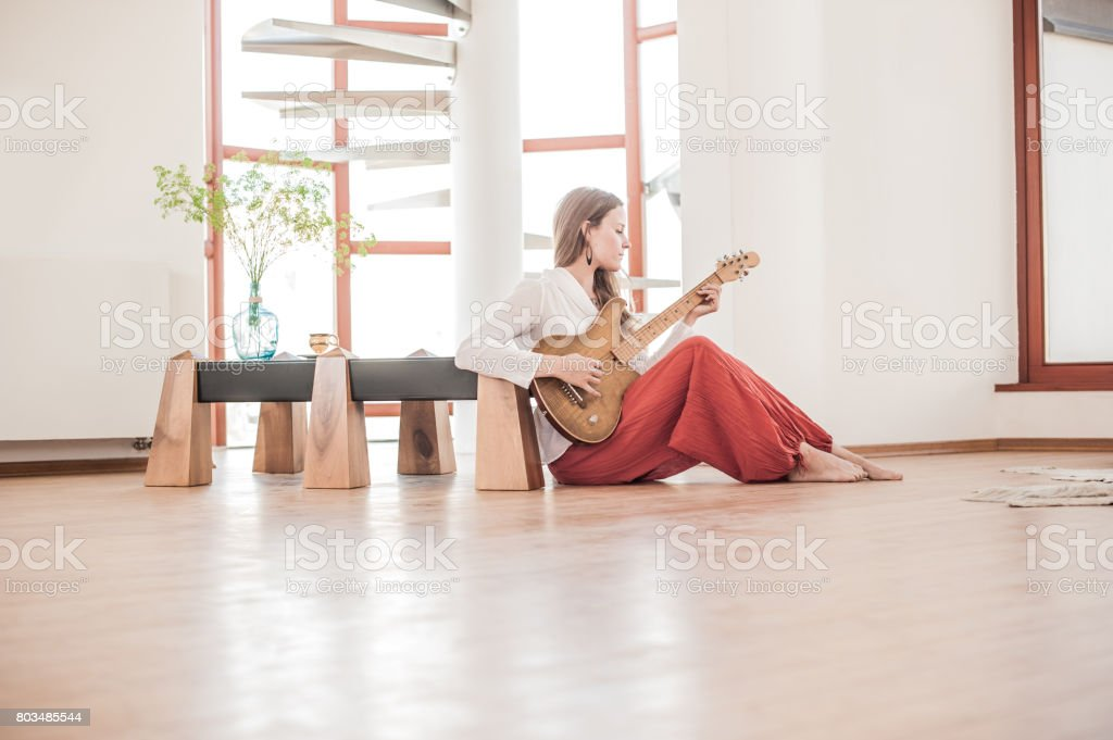 Young Woman Playing Guitar in the New Home stock photo