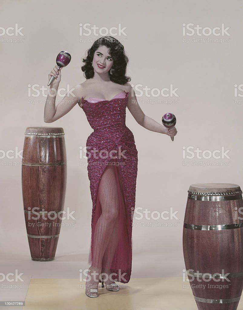 Young woman playing maracas, smiling stock photo