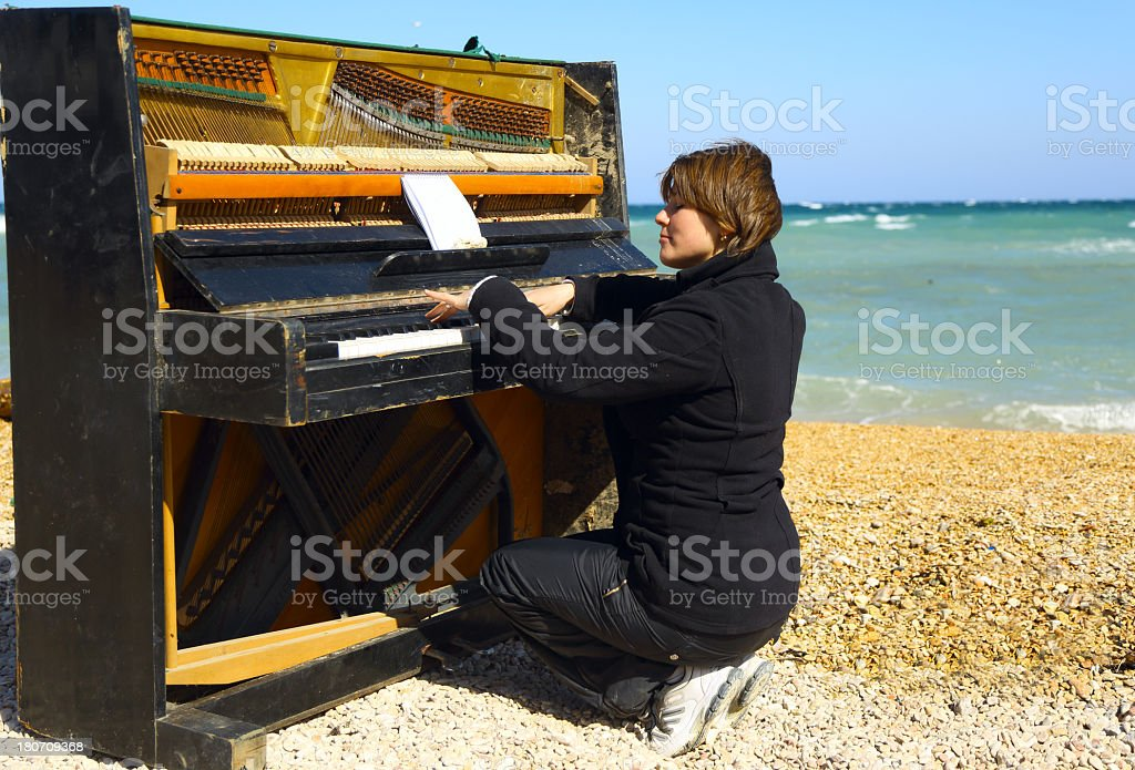 young woman playing on an old piano royalty-free stock photo