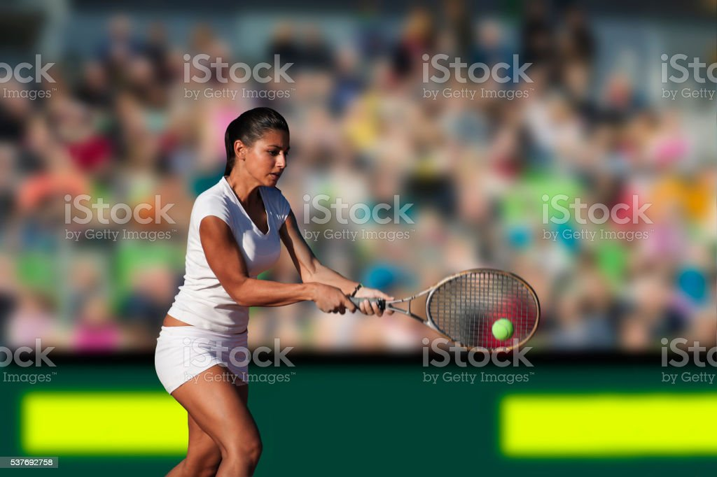 Young Woman Playing Tennis at Main Court stock photo