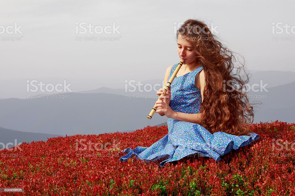 Young woman playing the flute in mountains stock photo