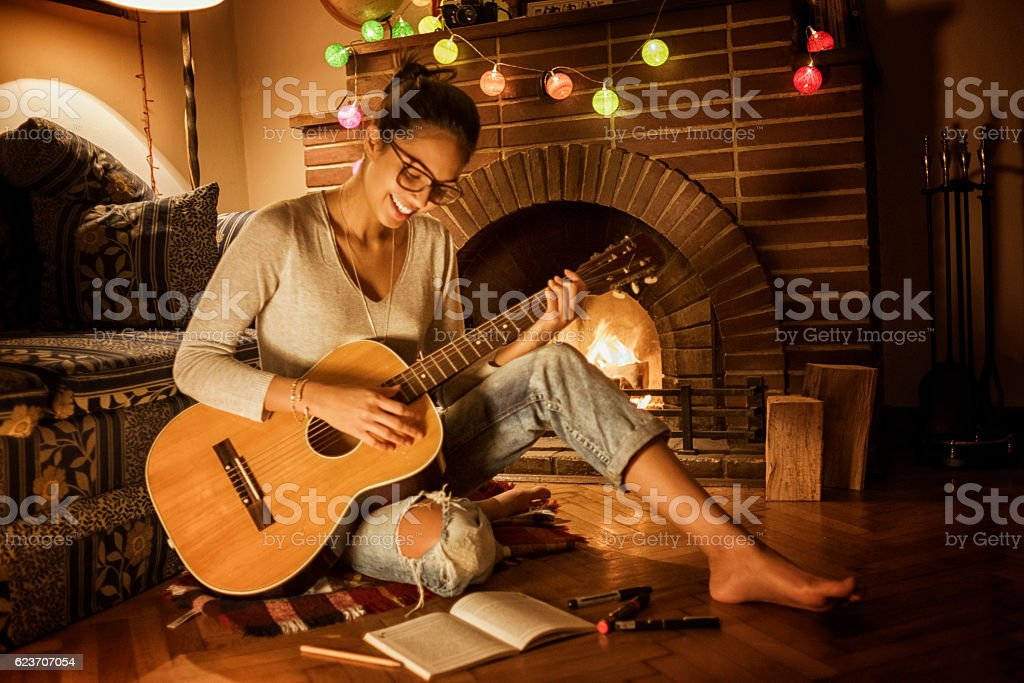 young woman playing the guitar next to the fireplace stock photo