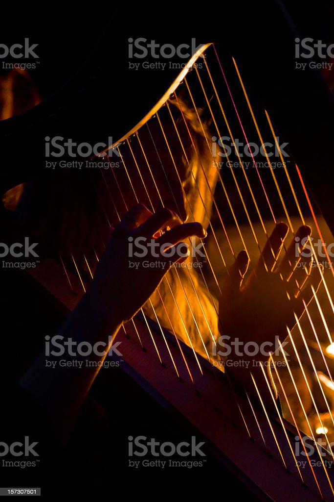 Young woman playing the harp stock photo
