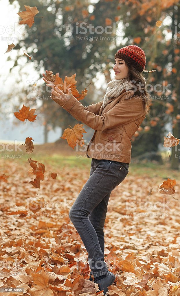young woman playing with autumn leaves royalty-free stock photo