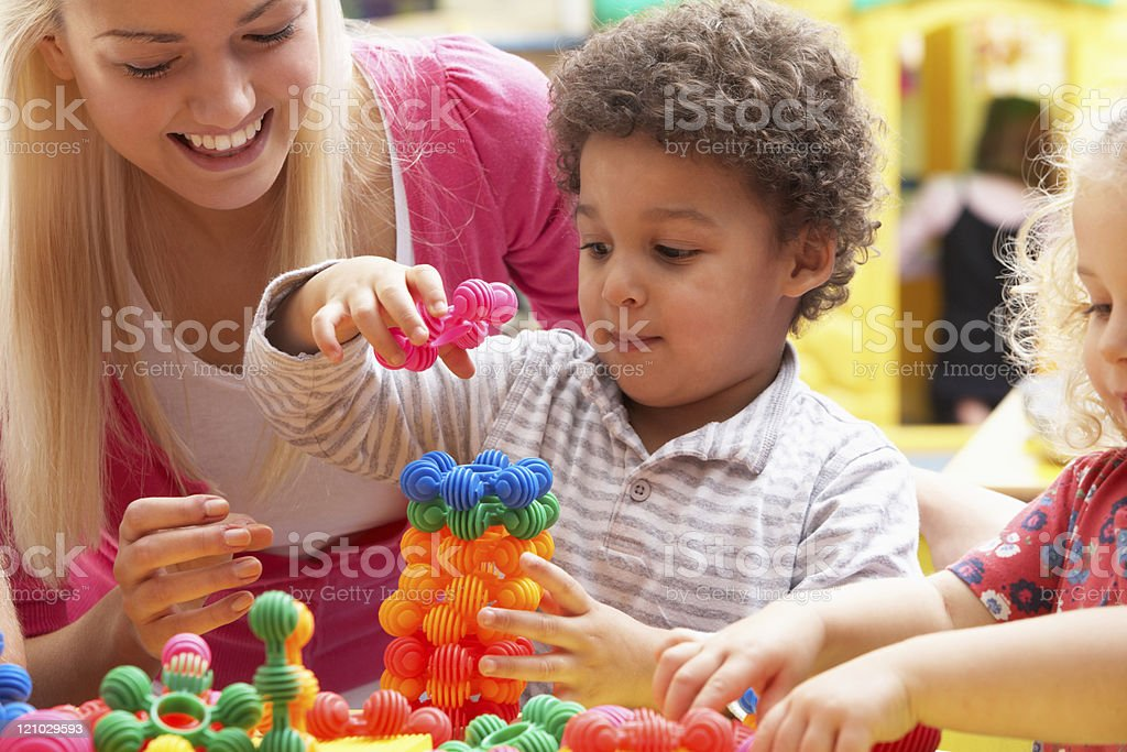 Young woman playing with boy in nursery school stock photo