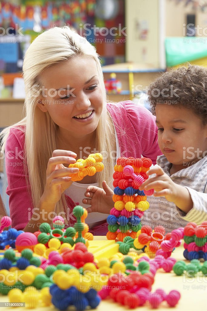 Young woman playing with boy stock photo