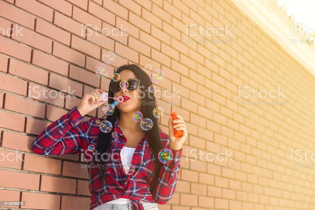 Young woman playing with bubble close to wall stock photo