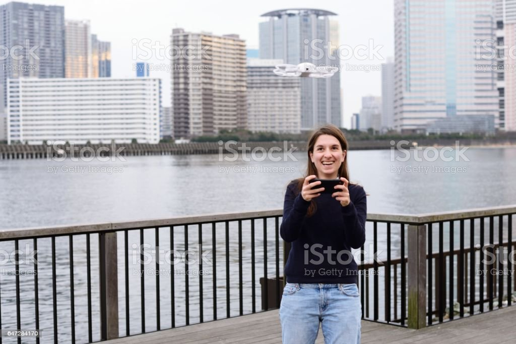 Young woman playing with drone stock photo