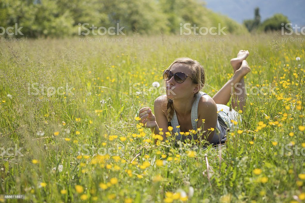 Young woman playing with flowers in the field stock photo