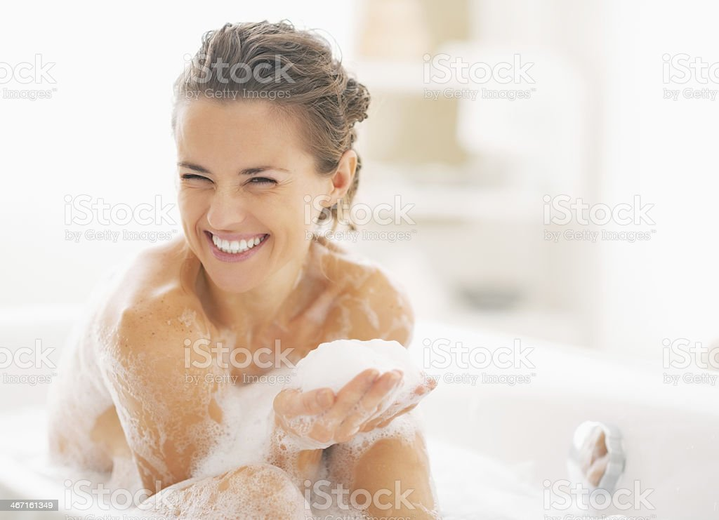 portrait of happy young woman playing with foam in bathtub stock photo