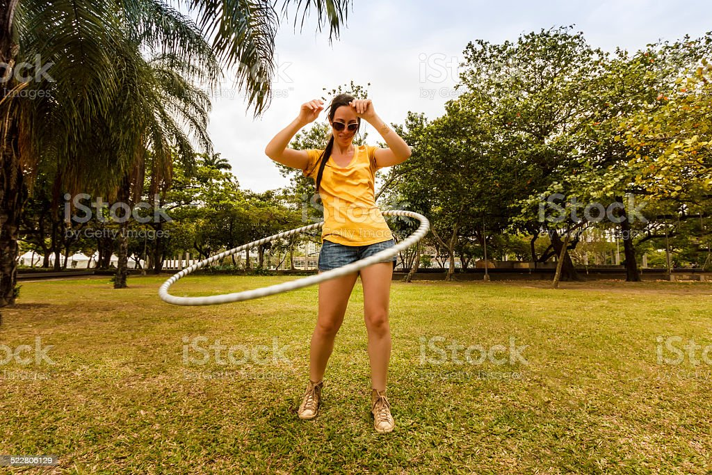 Young Woman Playing with Hula Hoop in Park stock photo