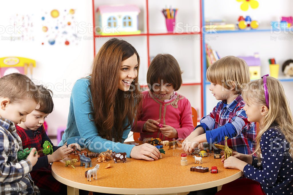 Young woman playing with kids in nursery school stock photo