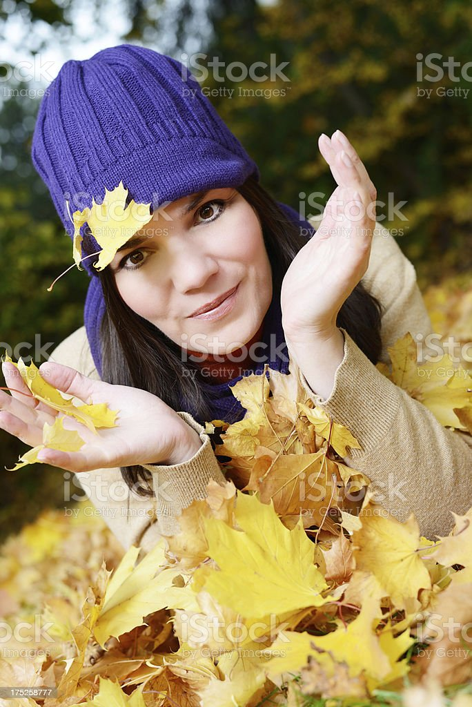 Young woman playing with leafs in autumn royalty-free stock photo