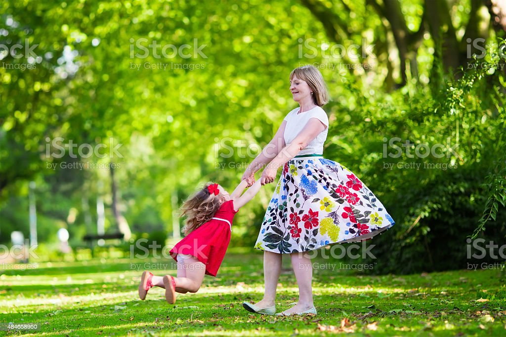 Young woman playing with little girl in a park stock photo