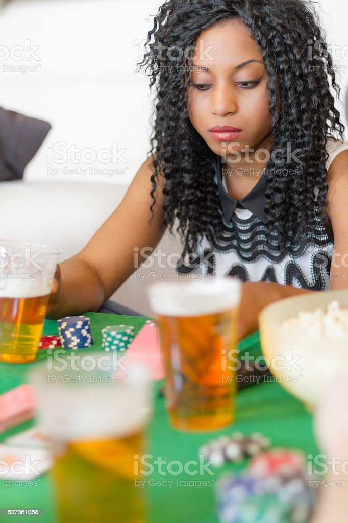 Young woman Plays Poker at home with friends stock photo