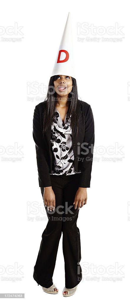 Young woman plays the fool, grimacing in dunce cap royalty-free stock photo