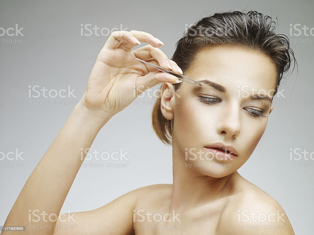 Young woman plucking her eyebrows with tweezers stock photo