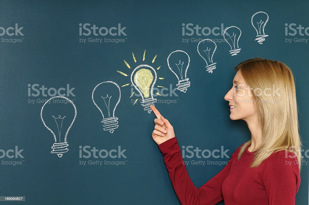 Young Woman Pointing a Light Bulb royalty-free stock photo