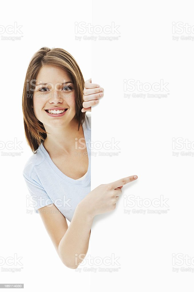 Young Woman Pointing Around a Corner - Isolated royalty-free stock photo