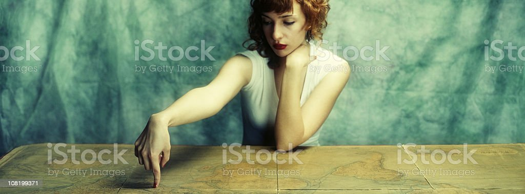 Young Woman Pointing Finger on Vintage Map royalty-free stock photo