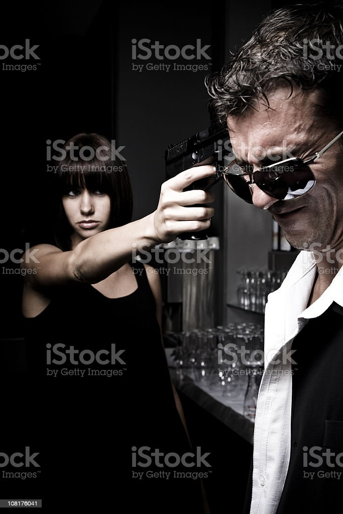 Young Woman Pointing Gun at Head of Grimacing Man royalty-free stock photo