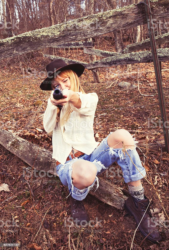 Young woman pointing gun at the camera stock photo