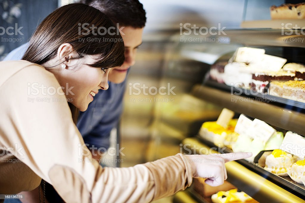 Young woman pointing on cakes in confectionery stock photo