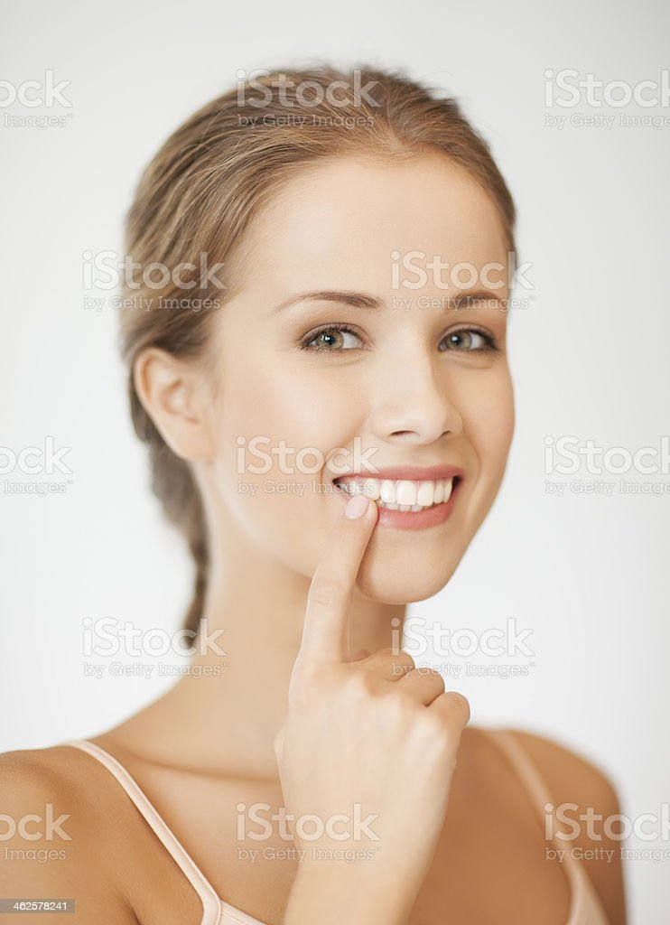 Young woman pointing with one finger to her white teeth stock photo