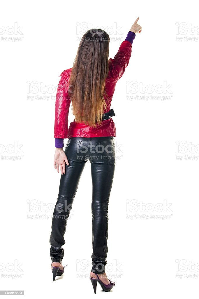 Young woman points at wall. The rear view royalty-free stock photo