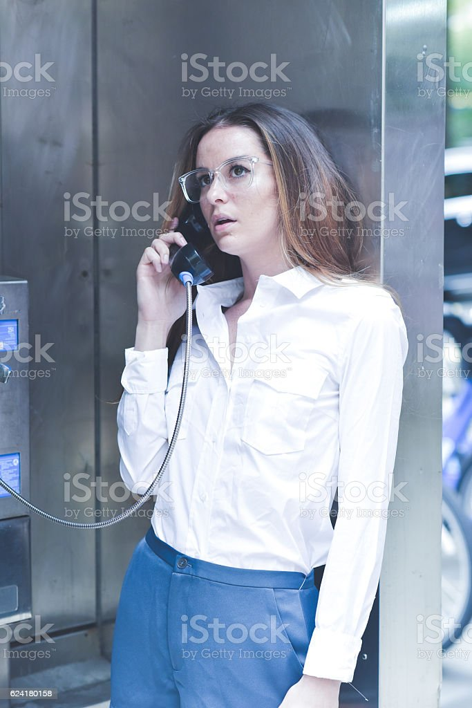Young Woman Ponders while Talking on Payphone stock photo