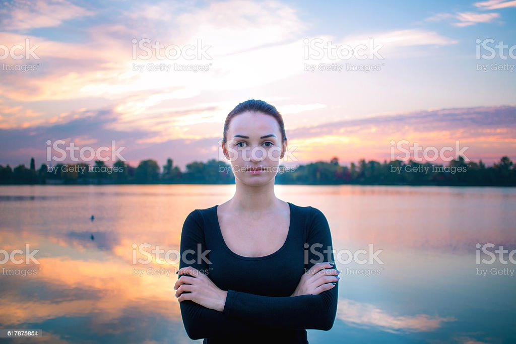 Young woman portrait in early morning at colorful sunrise background stock photo