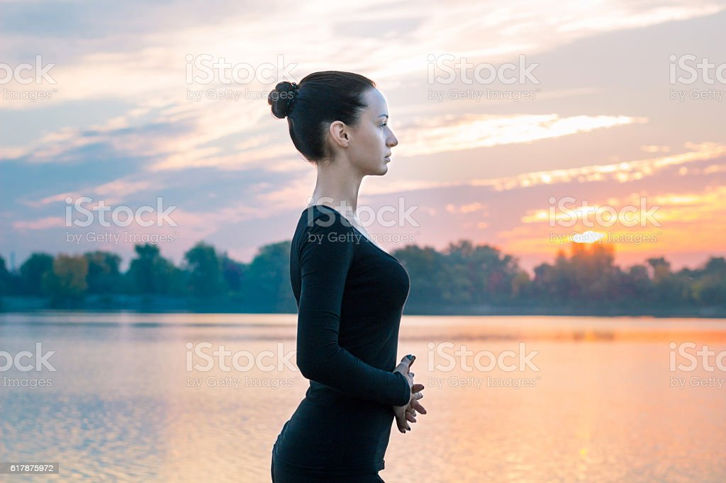 Young woman portrait in early morning during colorful sunrise stock photo