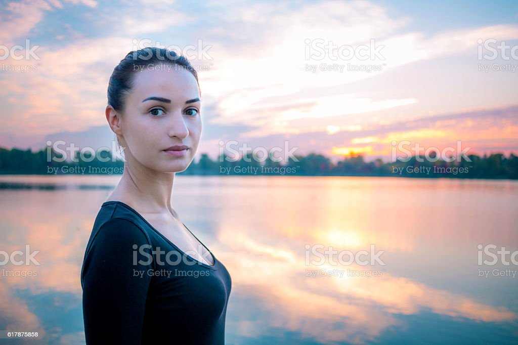 Young woman portrait in morning at colorful sunrise background stock photo