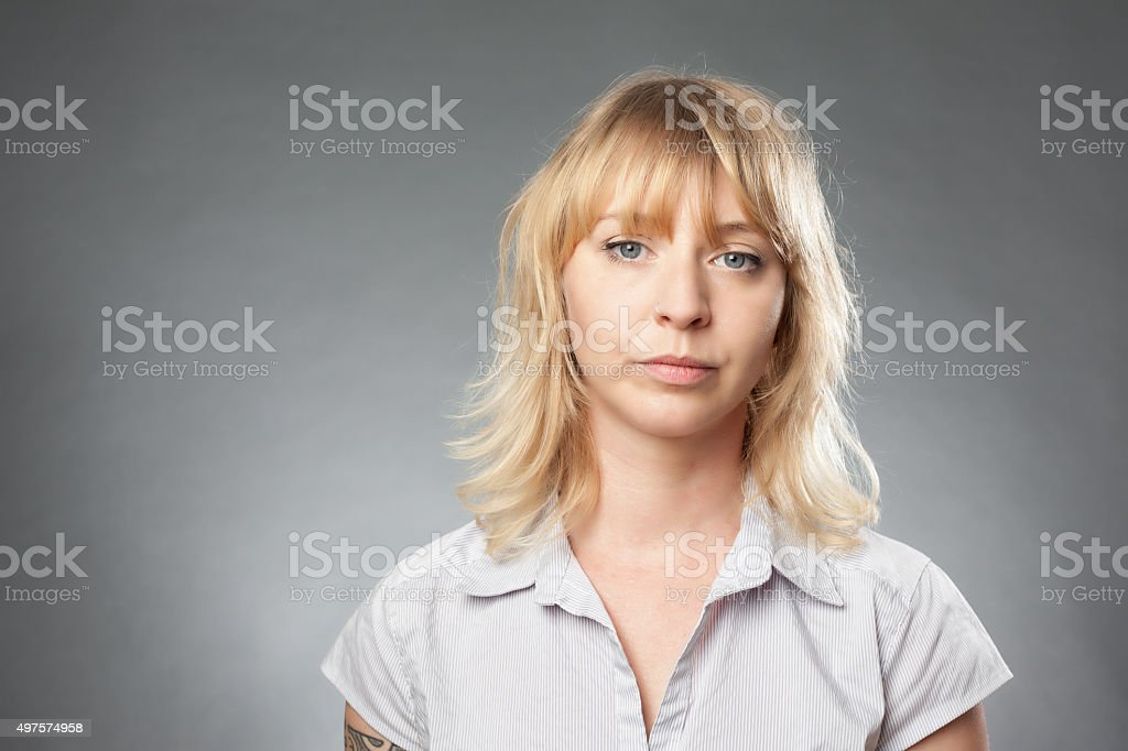 Young woman portrait on grey background, neutral expression stock photo