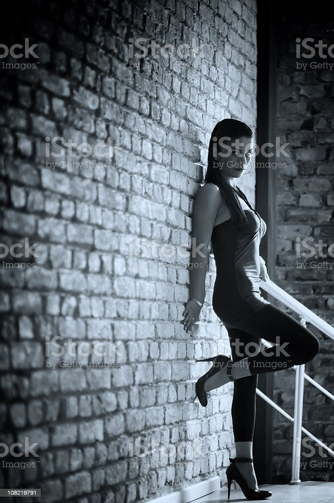 Young Woman Posing Against Brick Wall, Black and White Toned