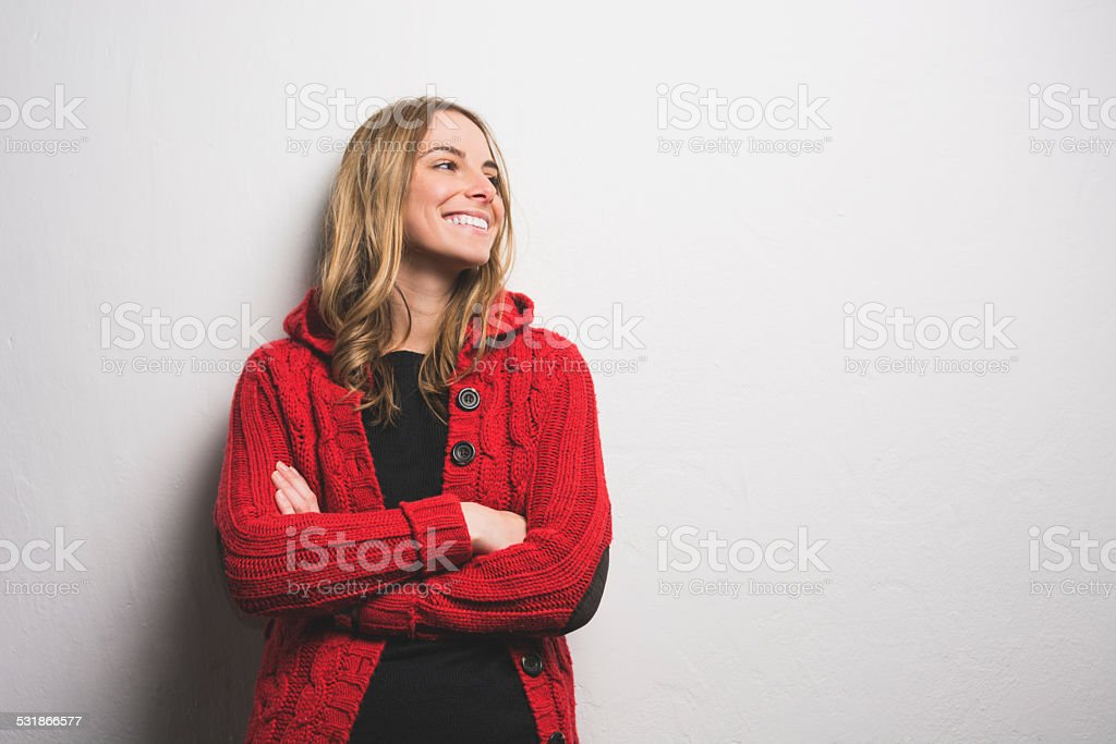 Young woman posing against the wall stock photo