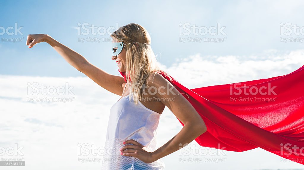 Young woman posing as superhero over blue sky stock photo