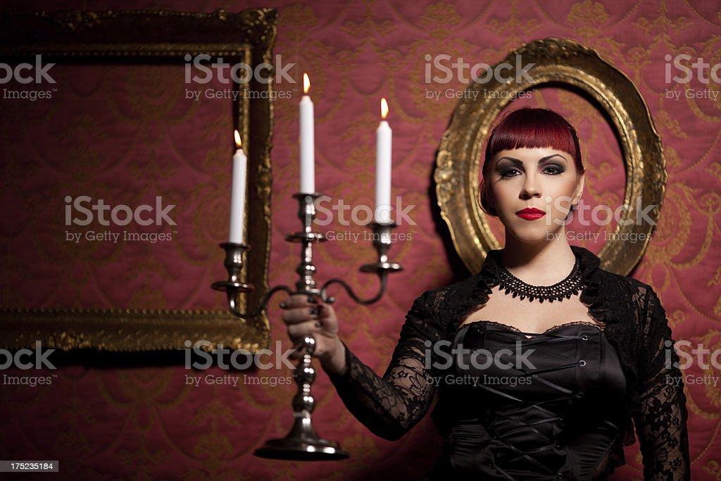 Young woman posing dressed in gothic style with candlestick royalty-free stock photo