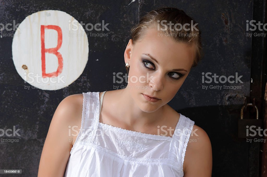 Young woman posing in front of black wall outdoors royalty-free stock photo
