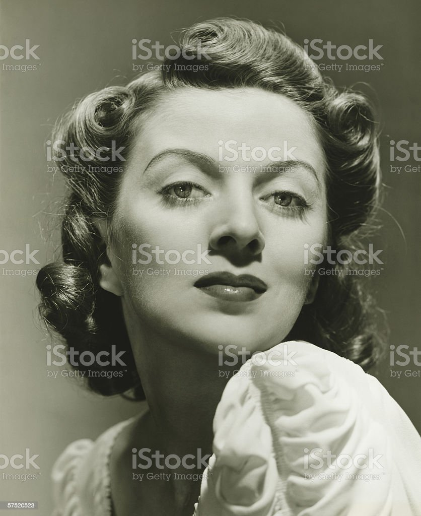 Young woman posing in studio, (B&W), portrait, close-up stock photo