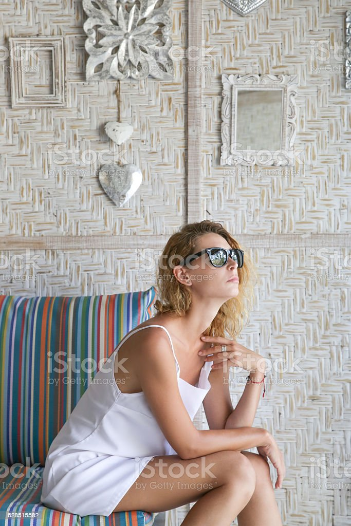 Young woman posing in white dress and black glasses stock photo