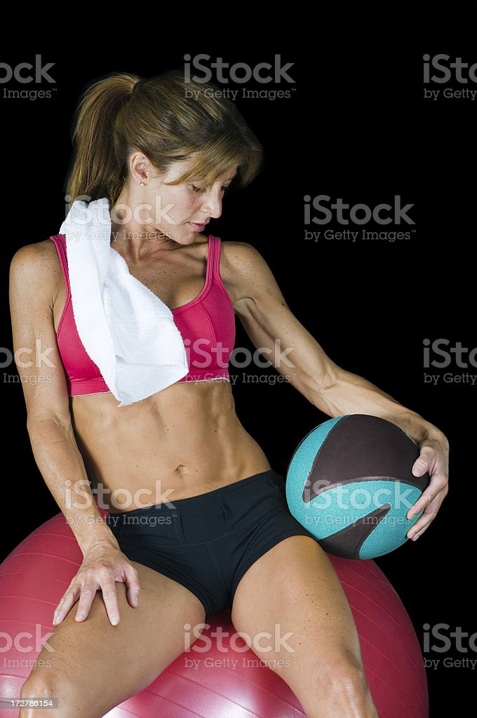 Young woman posing on a workout ball for fitness magazine royalty-free stock photo