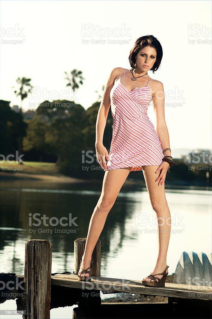 Young Woman Posing on Dock with Palm Trees in Background royalty-free stock photo