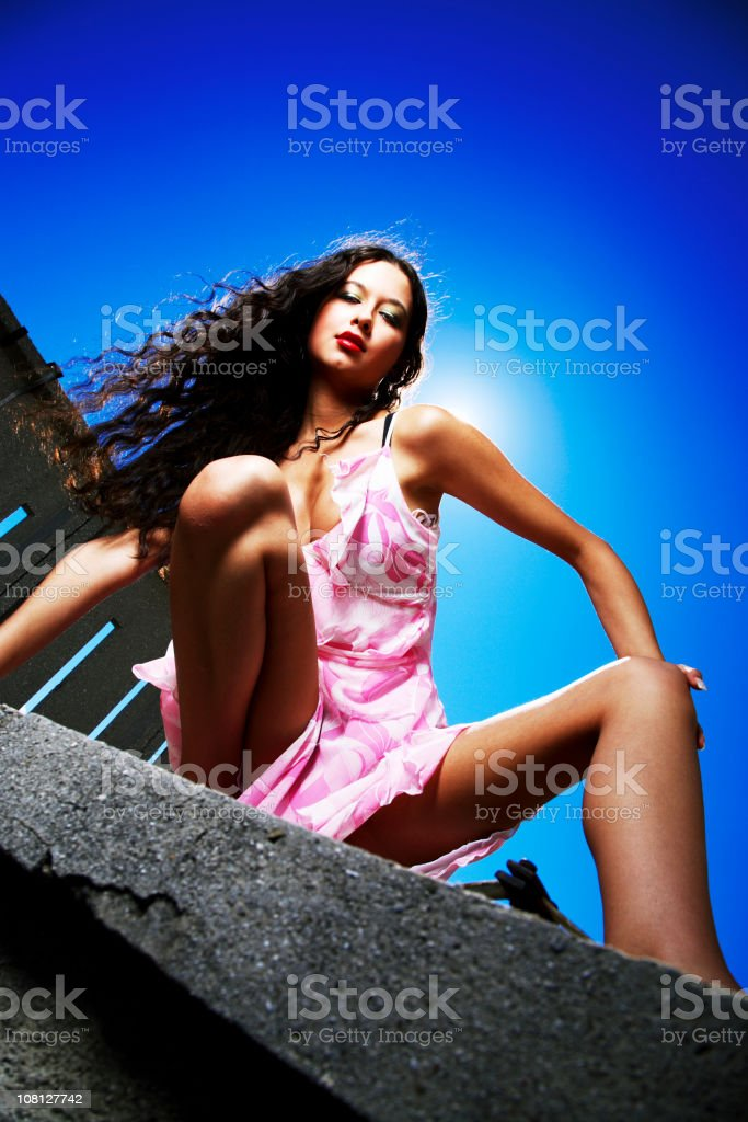 Young Woman Posing on Ledge Outside and Wearing Dress royalty-free stock photo