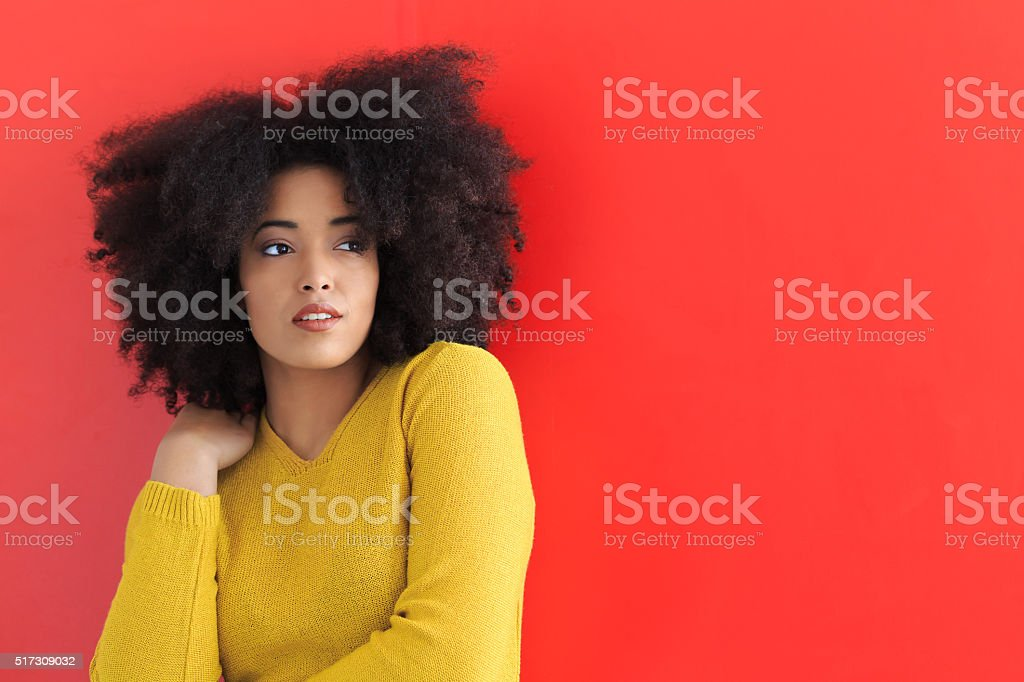 Young woman posing on red background stock photo