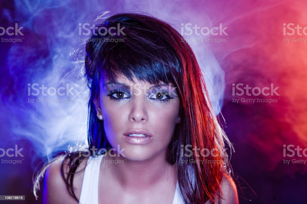 Young Woman Posing with Colorful Fog Behind Her royalty-free stock photo