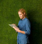 Young woman posing with tablet by green wall
