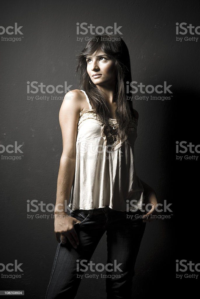 Young Woman Posing with Thumbs In Jean Pockets stock photo