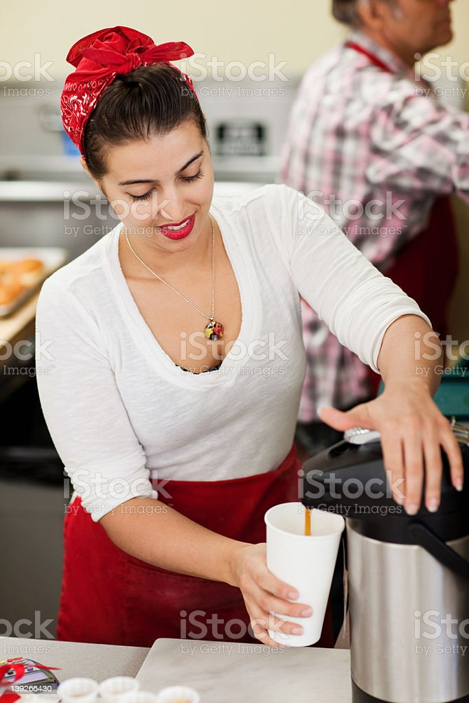 Young woman pouring fresh coffee into disposable cup stock photo